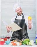 Cocinero barbudo del hombre que cocina la comida El individuo ley? recetas del libro Concepto de los artes culinarios El hombre a imagen de archivo
