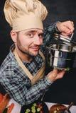 Cocinero barbudo del cocinero que prueba la sopa de una cacerola Imágenes de archivo libres de regalías
