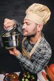 Cocinero barbudo del cocinero que prueba la sopa de una cacerola Foto de archivo libre de regalías
