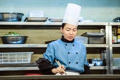 Cocinero blanco de trabajo de la hembra del texto Foto de archivo