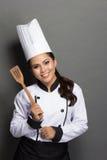 Cocinero bonito de la mujer en la acción Imagenes de archivo
