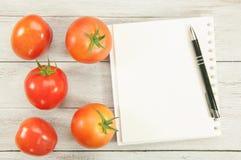 Cocinero Book Guide y tomate Imágenes de archivo libres de regalías