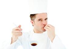 Cocinero caucásico de los jóvenes que prueba una sopa deliciosa Fotos de archivo libres de regalías