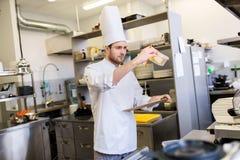 Cocinero con el tablero que hace inventario en la cocina foto de archivo libre de regalías