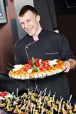 Cocinero con la comida en las placas Imagen de archivo libre de regalías