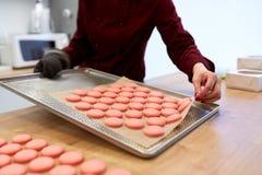 Cocinero con los macarons en la bandeja del horno en la confitería Fotos de archivo libres de regalías