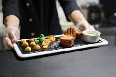 Cocinero con los salmones asados a la parrilla deliciosos envueltos imagen de archivo libre de regalías