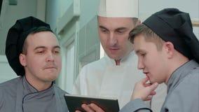 Cocinero concentrado que muestra a sus aprendices algo en la tableta digital almacen de video