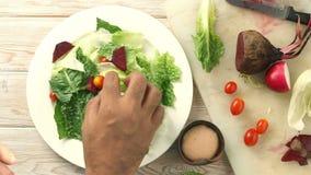 Cocinero consciente de la mano de la salud que lanza una ensalada verde orgánica sabrosa, visión superior almacen de video