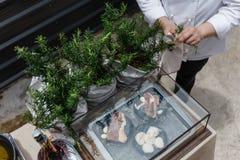 Cocinero Cut Rosemary Leaves por el cuchillo para hacer a Rosemary Oil Imagen de archivo