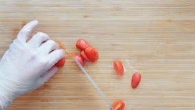Cocinero Cutting Chopping Cherry Tomatoes On una tabla de cortar de madera Visión superior almacen de metraje de vídeo