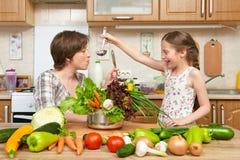 Cocinero de la madre y de la hija y sopa del gusto de verduras Interior casero de la cocina Padre y niño, mujer y muchacha Estafa foto de archivo