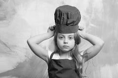 Cocinero de la muchacha o bebé feliz en el sombrero del cocinero, cocinando el delantal Fotografía de archivo