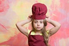 Cocinero de la muchacha o bebé feliz en el sombrero del cocinero, cocinando el delantal Imagen de archivo