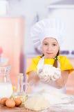 Cocinero de la muchacha que sostiene una pila de harina, huevos Imagenes de archivo