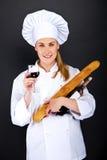 Cocinero de la mujer con pan francés y copa de vino sobre fondo oscuro Foto de archivo