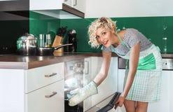 Cocinero de la mujer de la sonrisa que fríe o que asa Foto de archivo libre de regalías