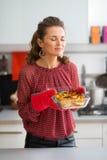 Cocinero de la mujer en cocina que goza del olor de la calabaza asada imagenes de archivo