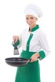 Cocinero de la mujer en el sartén que se sostiene uniforme aislado en blanco Fotografía de archivo