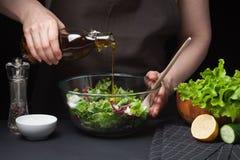 Cocinero de la mujer en la cocina que prepara la ensalada vegetal Consumición sana Adiete el concepto Una manera de vida sana Par fotografía de archivo libre de regalías