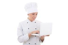 Cocinero de la mujer joven en uniforme con el ordenador portátil aislado en blanco Imagen de archivo