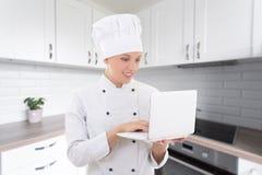 Cocinero de la mujer joven en uniforme con el ordenador portátil en cocina moderna Fotos de archivo