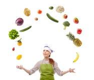 Cocinero de la mujer que hace juegos malabares con las frutas y verduras Foto de archivo