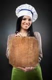 Cocinero de la mujer que lleva a cabo a un tablero con el copyspace Fotos de archivo libres de regalías