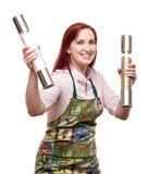 Cocinero de la mujer que sostiene molinos de la sal y de pimienta Fotos de archivo