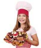 Cocinero de la niña con el postre de las tortas Fotografía de archivo