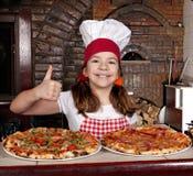 Cocinero de la niña con la pizza y el pulgar para arriba Imagen de archivo