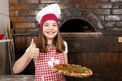 Cocinero de la niña con la pizza y el pulgar para arriba en pizzería Imágenes de archivo libres de regalías