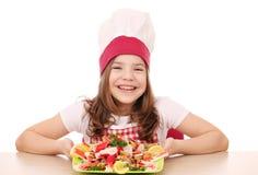 Cocinero de la niña con los mariscos en la tabla Foto de archivo libre de regalías