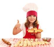 Cocinero de la niña con los rollos y el pulgar para arriba Imagenes de archivo
