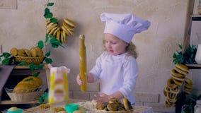 Cocinero de la niña que se divierte que juega con pasta en la decoración de la cocina