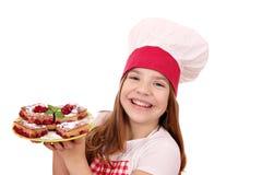Cocinero de la niña con la empanada de la cereza en la placa Imagenes de archivo