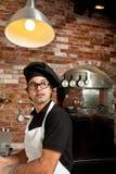 Cocinero de la pizza que se coloca en el funcionamiento de la cocina Fotos de archivo