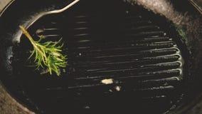 Cocinero de las hierbas que revuelve la cacerola asada a la parrilla romero del ajo almacen de video