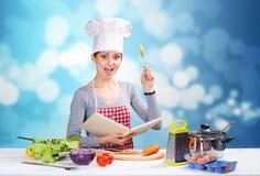 Cocinero de sexo femenino con el libro de cocina y una cuchara de madera en fondo azul foto de archivo