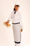 Cocinero de sexo femenino con los mízcalos y el delantal foto de archivo