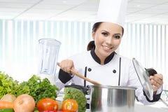 Cocinero de sexo femenino Cooking en la cocina Foto de archivo