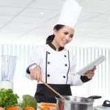 Cocinero de sexo femenino Cooking en la cocina Fotos de archivo