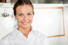 Cocinero de sexo femenino feliz In Kitchen Imágenes de archivo libres de regalías