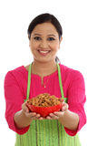 Cocinero de sexo femenino feliz que sostiene un cuenco de almendras contra blanco Fotos de archivo