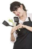 Cocinero de sexo femenino hermoso joven que lleva el delantal negro Imagenes de archivo