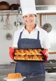 Cocinero de sexo femenino Holding Baked Bread Imagenes de archivo