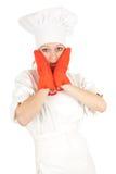 Cocinero de sexo femenino joven asustado con los guantes rojos de la cocina Foto de archivo libre de regalías