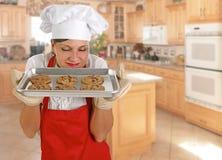 Cocinero de sexo femenino joven con las galletas imagen de archivo