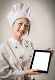Cocinero de sexo femenino joven Holding Tablet con la pantalla en blanco Imagenes de archivo