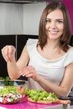 Cocinero de sexo femenino joven que hace una ensalada fresca Imágenes de archivo libres de regalías